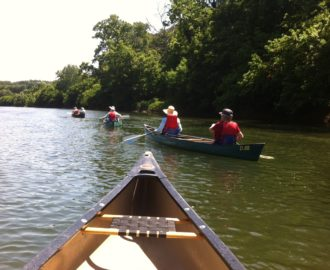 someone in a canoe took picture of three canoes with friends up ahead in the water Downriver Canoe Company Shenandoah Valley River