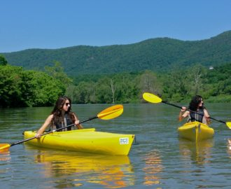 two sisters navigate their kayaks with paddles Downriver Canoe Company Shenandoah Valley River