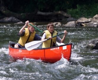 two young boys navigating the waves of the water in their canoe Downriver Canoe Company Shenandoah Valley River