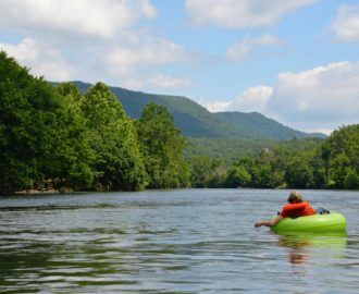 a young person tubing down very calm waters while enjoying the scenery Downriver Canoe Company Shenandoah Valley River